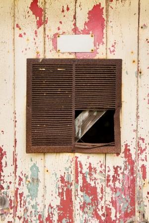 오래 된 필 링 도어 배경에서 오래 된 녹슨 공기 환기구