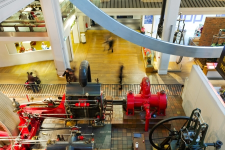 LONDON, UK - 25th November, 2012: People walking past a farming machinery exhibit in the main hall of the London Science Museum.