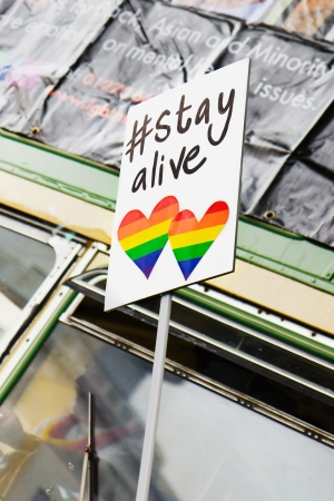 BRIGHTON, UK - September 1st, 2012  A  stayalive sign with rainbow hearts being held by one of the many participants in Brightons annual Gay Pride parade on 1st September 2012