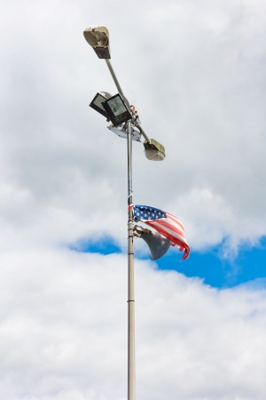 American flag tied to an old lamp post with a loud speaker