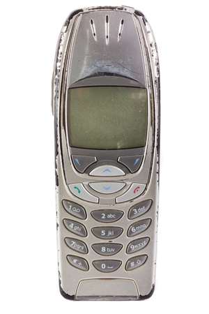 An old obsolete worn out cell phone being held over white
