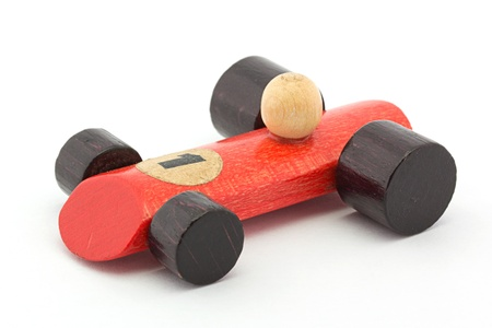 Small red wooden toy racing car over white