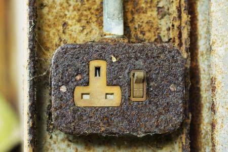 Old rusty 3 pin plug socket on a rusty beam Stock Photo - 17906970