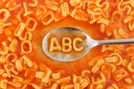 Pasta shaped ABC letters on a spoon within pasta shaped letters in tomato sauce