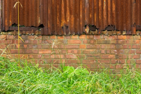 Background of rusty corrugated iron and brick wall in front of grass and weeds Stock Photo - 18280684