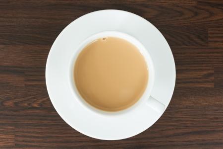 tazza di te: Vista aerea di tè in una tazza e piattino su un piano di lavoro in legno Archivio Fotografico