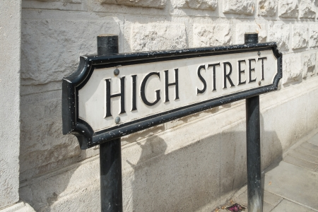 shops: A High Street road sign in front of a white wall
