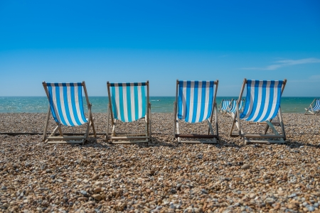 4 blue deck chairs on a pebble beach