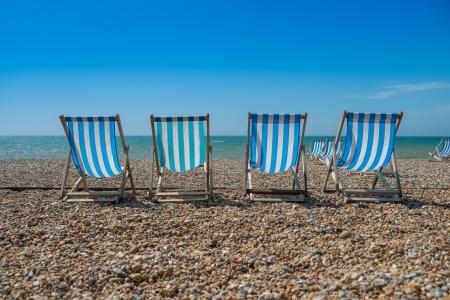 convés: 4 cadeiras azuis em uma praia de calhau