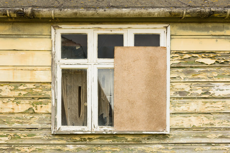 Partly boarded up window in a derelict house Stock Photo