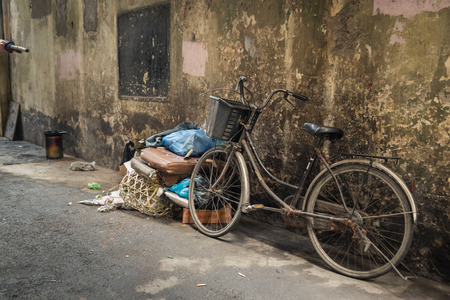 bycicle: An old bike left in a dirty alley