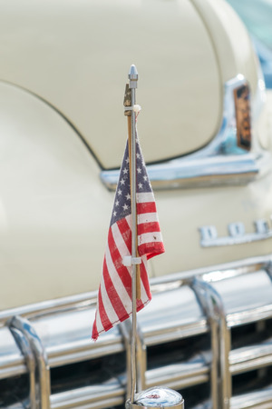 farm shop: WINDSOR, BERKSHIRE, UK- Augsut 4, 2013: An American flag mounted on the hood of a cream Dodge Coronet Classic car on show at Windsor Farm Shop International Classic Car Show in August 2013 Editorial