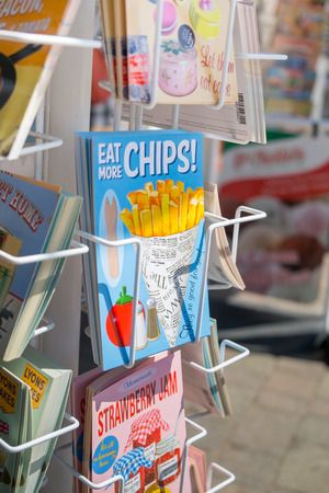 london to brighton: BRIGHTON, UK- JULY 28: Eat more chips postcard in a postcard rack on the seafront in Brighton, july 2013.