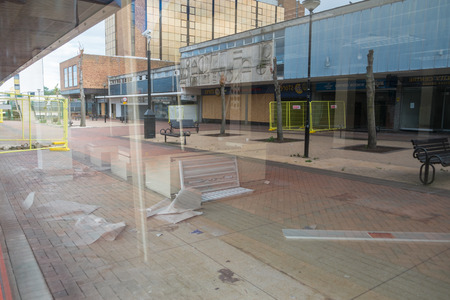 abandoned car: BRACKNELL, UK - AUGUST 11, 2013: An empty highstreet reflected in a window  in the Berkshire town of Bracknell. Awaiting demolition to make way for re-development.