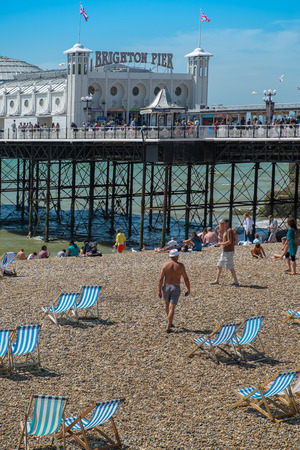 BRIGHTON, UK- JULY 28, 2013: People enjoying a rare sunny day on Brighton Beach in front of the famous Pier on July 28th, 2013. Editorial
