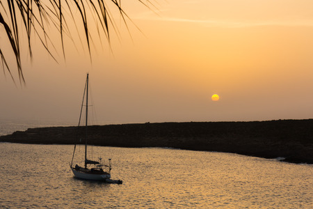 Silhouette of a small sailing boat at sunset. Stock Photo