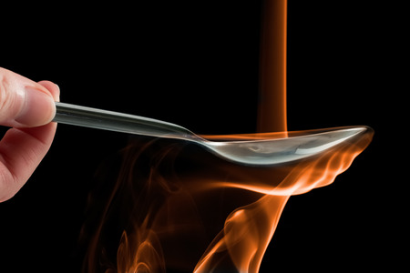 Smoke made to look like fire pouring on a spoon over a black background.