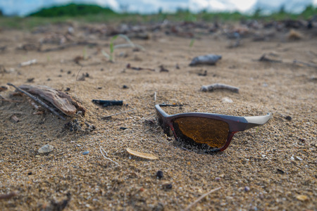 A pair of lost sunglasses on a deserted beach. Stock Photo