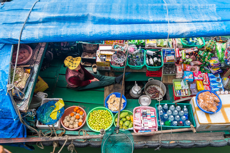 HALONG BAY, VIETNAM - JANUARY 29, 2014: A Vietnamese woman selling goods from her boat at Halong Bay in January 2014.