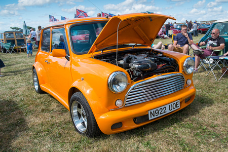 WINDSOR BERKSHIRE UK AUGUST 3 2014: An Orange Classic Mini with the bonnet open on show at a Classic Car Show in August 2013. Editorial