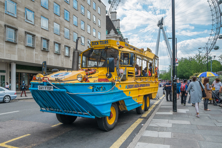 LONDON, UK- JULY 31, 2015: A London Duck Tours sightseeing bus pictured in-front of the London Eye. London Duck tours, using old 1940s recommissioned amphibious vehicles, have become a very popular way of seeing the city. Seen here in summer 2015. Editorial
