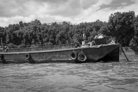disused: Black and white image of a rusty disused barge on the River.
