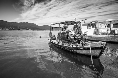 Small traditional Greek fishing boat in a port. Stock Photo