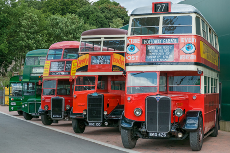 route master: WEYBRIDGE, SURREY, UK - AUGUST 18: A line of vintage red and green vintage buses outside the transport museum at Brooklands Motor Museum, Weybridge in 2013. Editorial