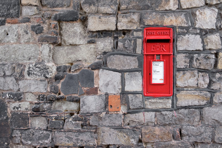 WINDSOR, UK - MARCH 18: A traditional iconic British post box in a stone wall in March 2017..