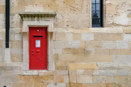 WINDSOR, UK - MARCH 18: A traditional iconic British post box in a stone wall in March 2017.