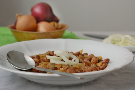 Cooked beans with the onion on the grey cloth background Reklamní fotografie