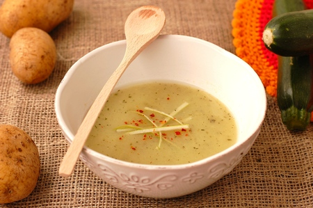 Zucchini soup with potatoes on the brown background
