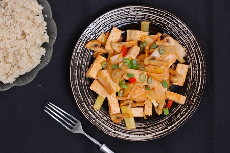 Tofu with the pepper and grouts on the black background, overhead view Reklamní fotografie