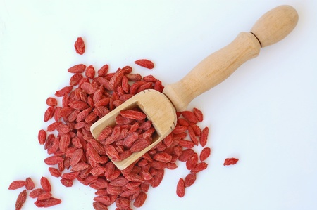 suger: Chinese goji in the wooden laddle on the white background, overhead horizontal view