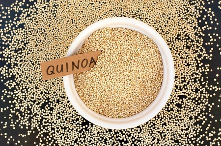coeliac: Quinoa in the bowl with the label on the black background, overhead horizontal view