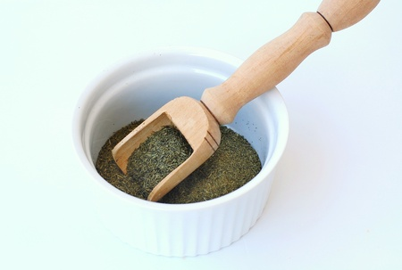 bawl: Dried dill in the bawl with the ladle, front horizontal view