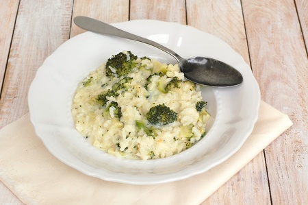 coeliac: Creamy risotto with broccoli on the cloth and wooden background, front horizontal view