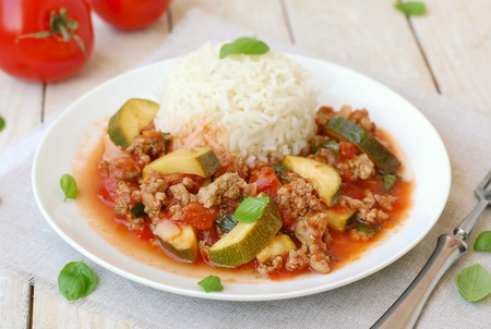 coeliac: Spicy mincemeat with tomatoes, basil and zucchini with basmati rice on the cloth on the wooden background Stock Photo