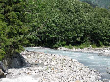 torrential glacier milk river on a sunny day making its way to the valley