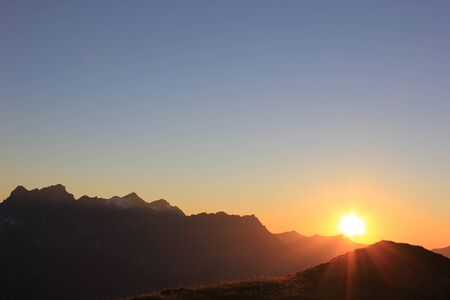 Colorful sunset in the swiss mountains with a raising sun behind the mountains