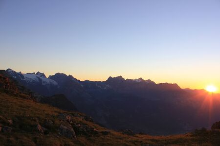 Colorful sunset in the swiss mountains with a raising sun behind the mountains Imagens