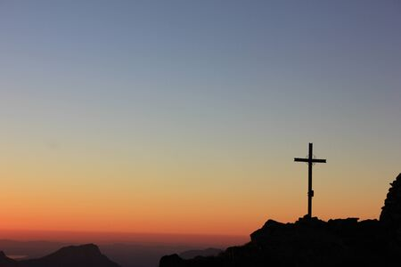 Colorful sunset in the swiss mountains with a wonderful red colored sky and a summit cross