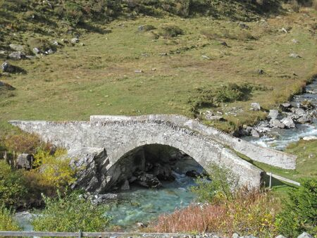 stonebridge over a mountain river on a sunny summer day