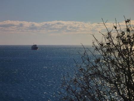 lejos: un gran barco lejos de la costa Foto de archivo