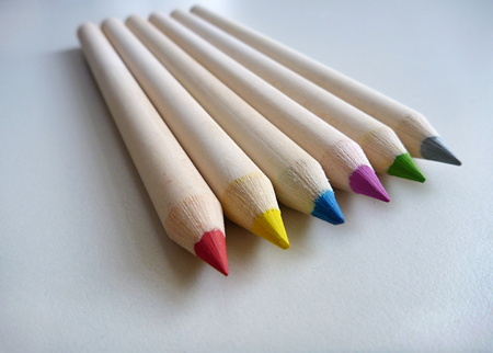 multi colored pencils on a white table background