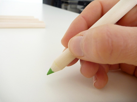 hand writing: a green pencil in a hand writing
