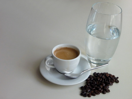 cup of water: a cup of fresh tasty coffee with coffee beans and a glass of water Stock Photo