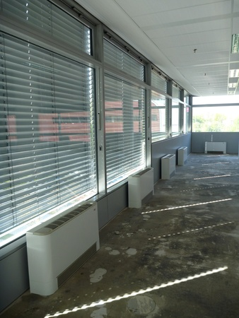 blinder: rays of light commimg through window in an empty office building