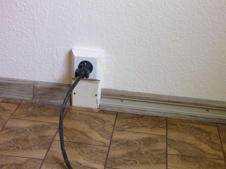 plugged in': black cable plugged in a socket at the floor