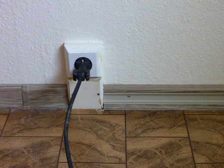 plugged in: black cable plugged in a socket at the floor